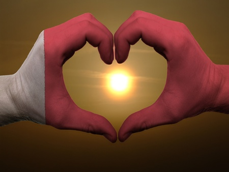 Gesture made by bahrain flag colored hands showing symbol of heart and love during sunrise photo