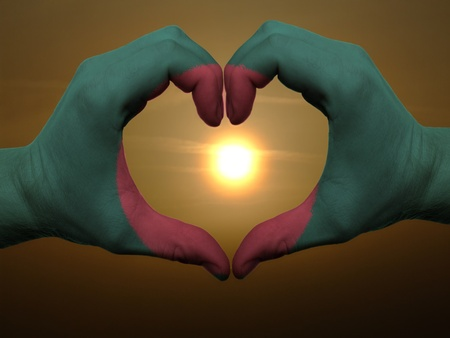 national colors: Gesture made by bangladesh flag colored hands showing symbol of heart and love during sunrise Stock Photo