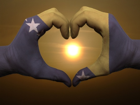 Gesture made by bosnia herzegovina flag colored hands showing symbol of heart and love during sunrise photo