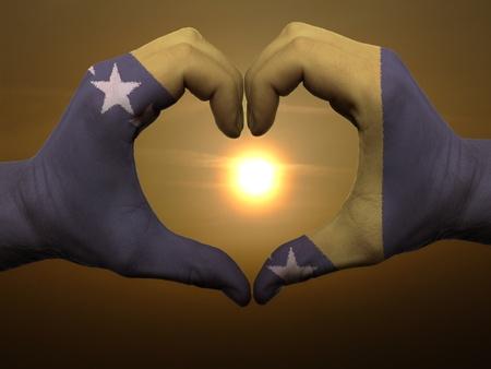 Geste von Bosnien-Herzegowina Flagge farbige Hände zeigen, Symbol des Herzens und der Liebe bei Sonnenaufgang gemacht