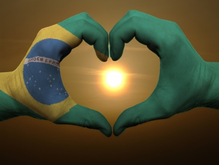 brazil: Gesture made by brazil flag colored hands showing symbol of heart and love during sunrise