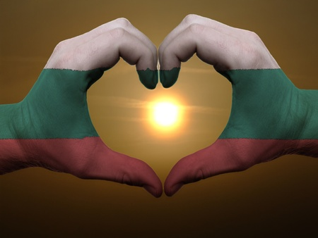 Gesture made by bulgaria flag colored hands showing symbol of heart and love during sunrise photo