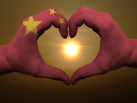 Gesture made by china flag colored hands showing symbol of heart and love during sunrise photo