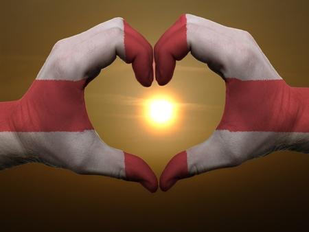 drapeau angleterre: Geste fait par des mains Drapeau de l'Angleterre de couleur indiquant le symbole du coeur et de l'amour pendant le lever du soleil