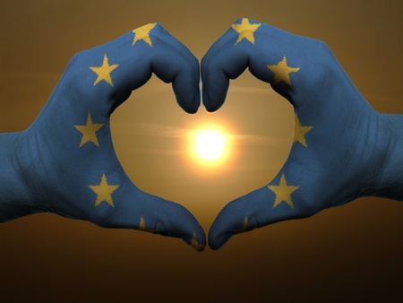 Gesture made by europe flag colored hands showing symbol of heart and love during sunrise photo