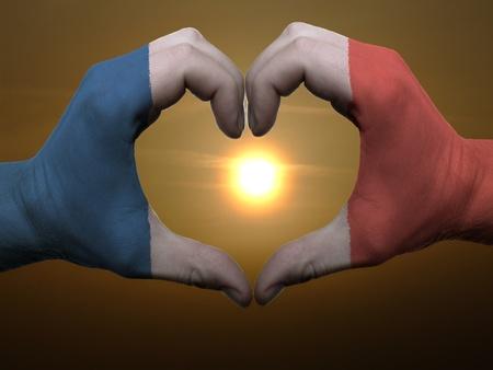 bandera francia: Gesto hecho por Francia manos bandera del color que muestra el s�mbolo del coraz�n y el amor durante el amanecer