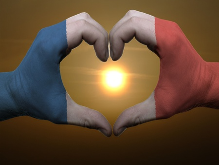Gesture made by france flag colored hands showing symbol of heart and love during sunrise photo