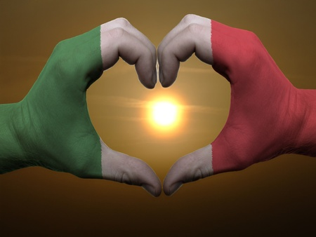Gesture made by italy flag colored hands showing symbol of heart and love during sunrise photo
