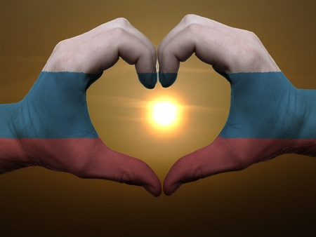 Gesture made by russia flag colored hands showing symbol of heart and love during sunrise Stock Photo - 11112129