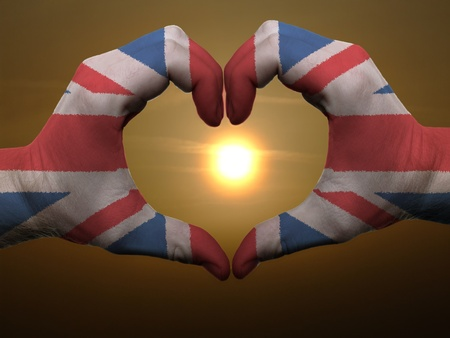 Gesture made by united kingdom flag colored hands showing symbol of heart and love during sunrise photo