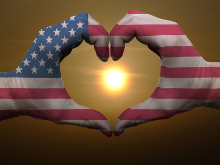 Gesture made by american flag colored hands showing symbol of heart and love during sunrise photo