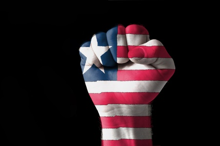 Low key picture of a fist painted in colors of liberia flag photo
