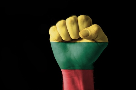 lithuanian: Low key picture of a fist painted in colors of lithuania flag