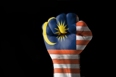Low key picture of a fist painted in colors of malaysia flag Фото со стока