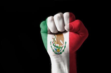 Low key foto van een vuist geschilderd in de kleuren van Mexico vlag Stockfoto