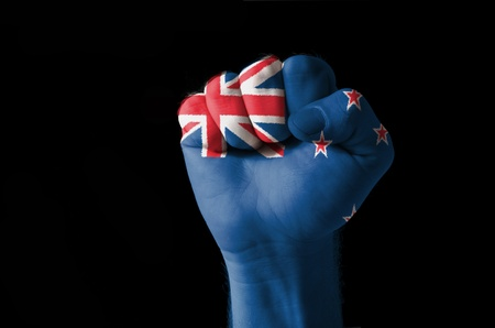 Low key picture of a fist painted in colors of new zealand flag photo