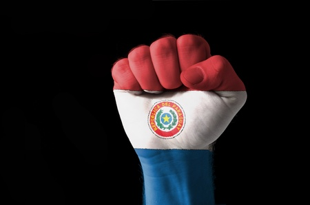 Low key picture of a fist painted in colors of paraguay flag photo