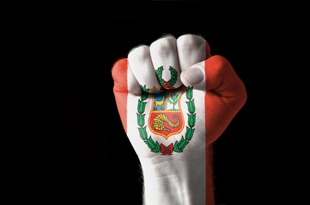 Low key picture of a fist painted in colors of peru flag photo