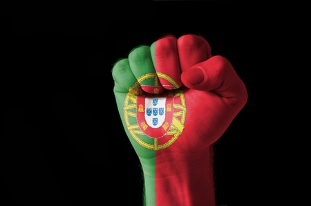 Low key picture of a fist painted in colors of portugal flag photo