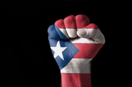 puerto rican: Low key picture of a fist painted in colors of puertorico flag Stock Photo