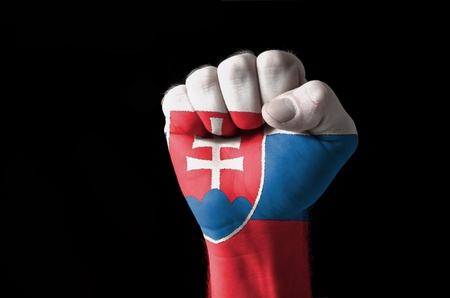 Low key picture of a fist painted in colors of slovakia flag