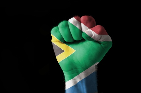Low key picture of a fist painted in colors of south africa flag Stock Photo