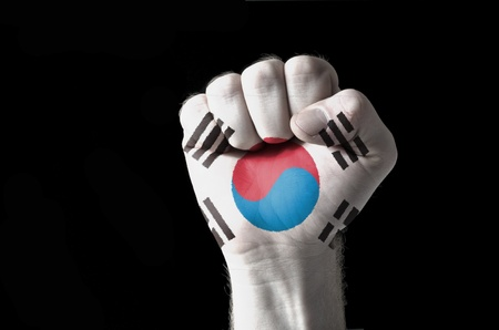 aggressor: Low key picture of a fist painted in colors of south korea flag Stock Photo