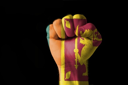 sri lankan flag: Low key picture of a fist painted in colors of srilanka flag Stock Photo