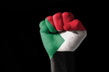 sudan: Low key picture of a fist painted in colors of sudan flag Stock Photo