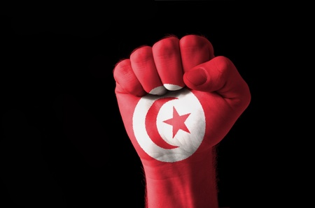 tunisian: Low key picture of a fist painted in colors of tunisia flag Stock Photo
