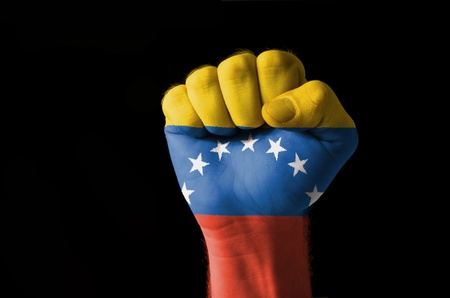 Low key picture of a fist painted in colors of venezuela flag photo