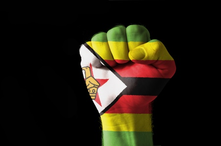 zimbabwe: Low key picture of a fist painted in colors of zimbabwe flag Stock Photo