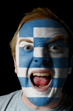 Low key portrait of an angry man whose face is painted in colors of greece flag photo