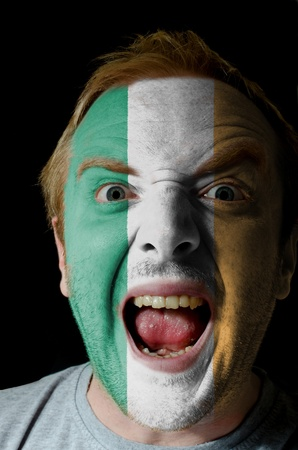 Low key portrait of an angry man whose face is painted in colors of irish flag Stock Photo - 11159101