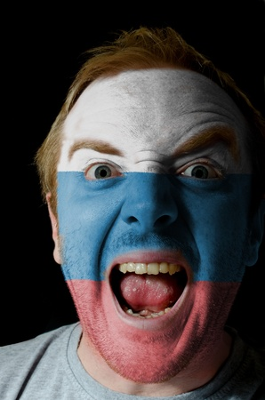 whose: Low key portrait of an angry man whose face is painted in colors of russia flag