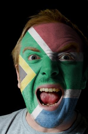 whose: Baja clave retrato de un hombre enojado, cuyo rostro est� pintado con los colores de la bandera de Sud�frica