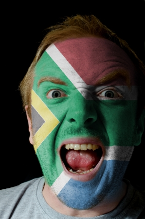 Low key portrait of an angry man whose face is painted in colors of south africa flag photo