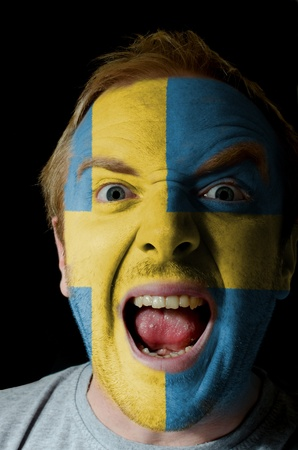 Low key portrait of an angry man whose face is painted in colors of sweden flag photo