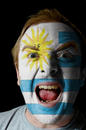 Low key portrait of an angry man whose face is painted in colors of uruguay flag photo