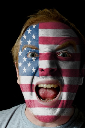 whose: Low key portrait of an angry man whose face is painted in colors of american flag