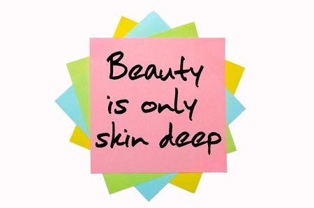 """texto """"La belleza es s�lo superficial"""", escrito por la mano en la fuente mont�n de notas adhesivas de color Foto de archivo - 11158711"""