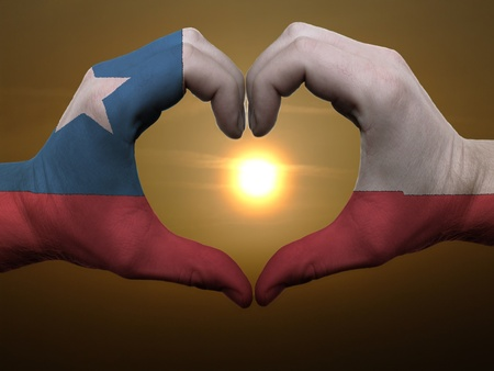 chilean flag: Gesto por parte de Chile manos la bandera de colores que muestra el s�mbolo del coraz�n y el amor durante el amanecer