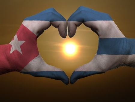 Gesture made by cuba flag colored hands showing symbol of heart and love during sunrise Фото со стока