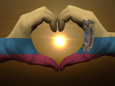 Gesture made by ecuador flag colored hands showing symbol of heart and love during sunrise