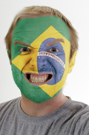 High key portrait of an angry man whose face is painted in colors of brazil flag photo