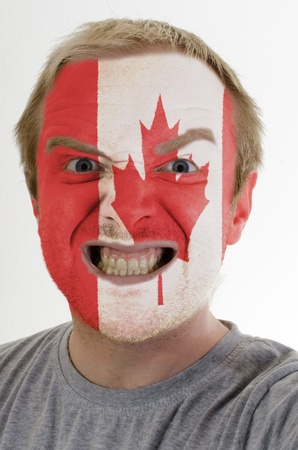 High key portrait of an angry man whose face is painted in colors of canada flag photo