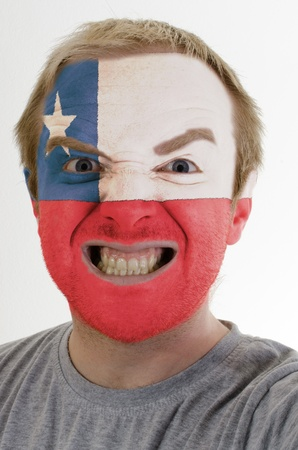 High key portrait of an angry man whose face is painted in colors of chile flag photo