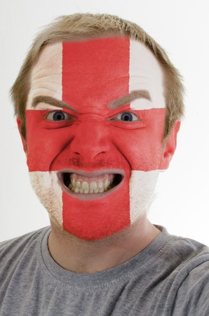 High key portrait of an angry man whose face is painted in colors of england flag photo