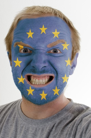 High key portrait of an angry man whose face is painted in colors of europe flag photo