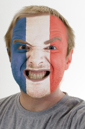 High key portrait of an angry man whose face is painted in colors of france flag photo